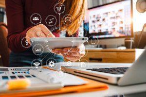 Imagem conceitual de uma pessoa manipulando um tablet, com diversos ícones saindo do aparelho, representando a difusão do conteúdo em diversos formatos multimídia