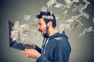 Imagem conceitual de uma pessoa olhando para um notebook e diversas notas de dinheiro saindo pela tela do monitor.