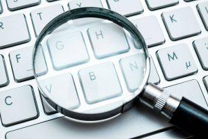 Imagem conceitual mostrando uma lupa em cima de um teclado, representando o trabalho de SEO para marketing de conteúdo